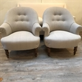 Pair of French tub chairs covered in Taupe linen with a buttoned back and brown turned beechwood legs. C1950.