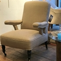 French chair with showing arms, covered in Taupe linen, with black turned legs and brass castors. C1940